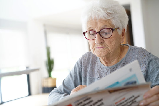 Portrait of old woman reading newspaper at home
