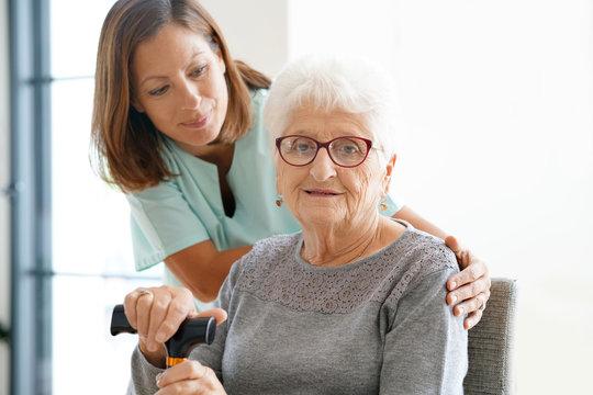 Nurse visiting old woman at home
