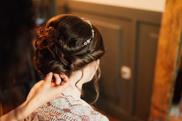 Hairdresser doing hairstyle for the bride