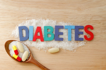 Diabetes concept. Colorful / colourful alphabet with word DIABETES with sugar and pills on wooden background.