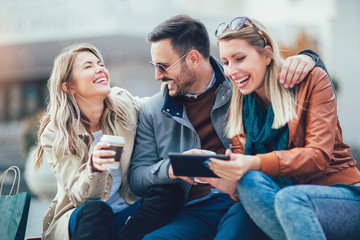Group of smiling friends with digital tablet outdoor