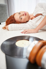 Young beautiful woman listen music with record in a living room