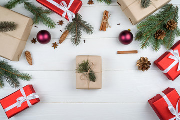 Christmas background with gift boxes, fir tree branches, pine cones, cinnamon sticks and stars anise on white wooden background, free space. Holiday greeting card, copy space. Flat lay, top view