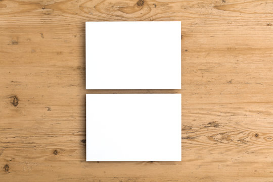 Blank white business card postcard flyer on a wooden background