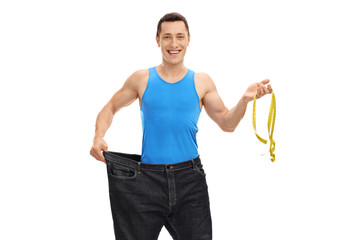 Man in a pair of oversized jeans holding a measuring tape