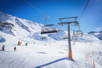 Sunny day in the Austrian Alps - ski tracks, ski lifts and snow mountains