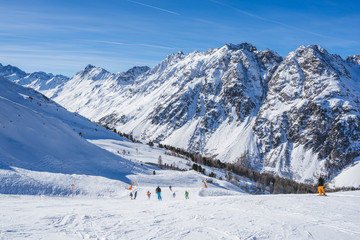 Sunny day in the Austrian Alps - ski tracks, ski lifts and snowy mountains
