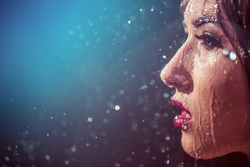 Close up portrait of sexy wet brunette girl wears black top under rain splashes