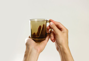 Male hand holding black empty glass mug. Isolated on gray background. Closeup
