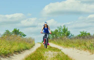 One young woman - an athlete in a helmet riding a mountain bike outside the city, on the road on a summer day.