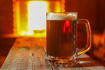 Beer in a glass mug against fireplace.