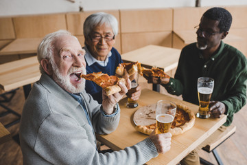 senior friends drinking beer with pizza