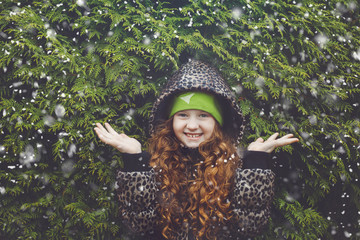 Little curly hair girl near green winter tree.