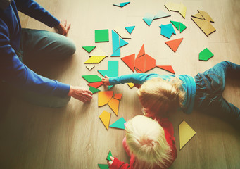 teacher and kids playing with geometric shapes puzzle
