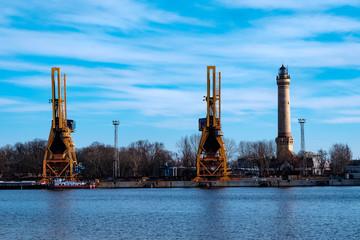 Ladekräne und Leuchtturm im Hafen von Swinemuende/Polen