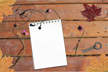 Mockup. Mahogany wood table with flowers, notepad, headphones and vintage key. Place for your text.