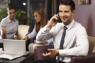 Businessman using mobile at hotel lobby