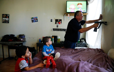 Natalia Rollins children (L) Randy, 4, and Noah,2, watch television as Bob Friedl, a senior project manager with Environmental Management Solutions of New York Inc., checks lead levels with an X-Ray fluorescence detector at their apartment in the Coney I