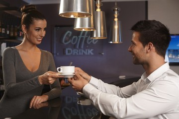 Pretty waitress serving businessman in bar