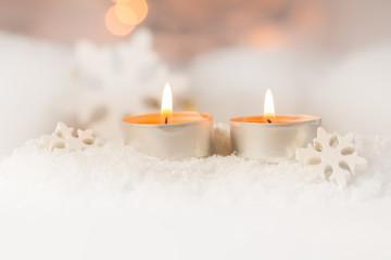 Zwei brennende Teelichte im Schnee