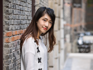 Portrait of beautiful young Chinese woman wearing white sweater and blue jeans standing in street and smiling at camera in Shanghai Xintiandi.