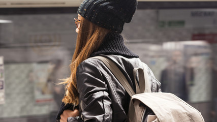 Young woman passenger in public train station in city