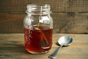 Red tea carafe on wooden background