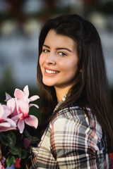 Attractive young woman working in greenhouse and enjoying in beautiful flowers.