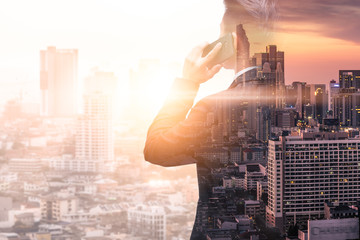 The double exposure image of the business man using a smartphone calling during sunrise overlay with cityscape image. The concept of modern life, business, city life and internet of things.