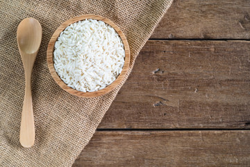 raw white sticky rice in wood bowl with wood spoon on gunny sack cloth on wooden table, top view with copy space