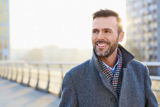 Happy man standing outdoors during sunny winter day