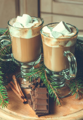 Christmas cups with hot chocolate, cocoa, decorated with spruce sprigs, cinnamon sticks and sweet black chocolate