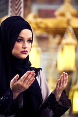 Young pretty muslim woman in hijab praying inside the mosque