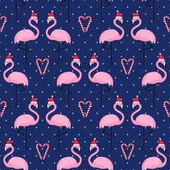 Flamingo in xmas hat with candy cane heart seamless pattern on blue polka dots background. Exotic New Year background. Christmas design for fabric, wallpaper, textile and decor.