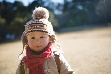 Little girl playing in a park in winter