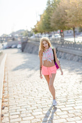 A young woman or girl walks on a summer European city