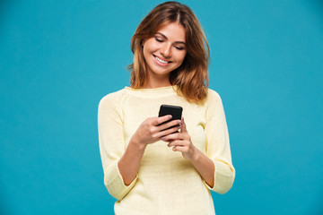 Smiling woman in sweater writing message on smartphone