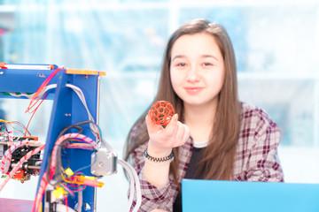 Girl schoolgirl with a 3D printer