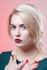 Blonde girl with pin-up makeup folded arms on the light pink background close-up