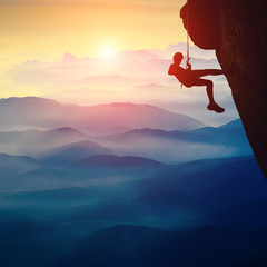 Silhouette of climber girl on a cliff