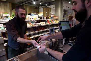 A shop holder gives back cash to a customer in Brussels