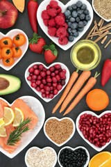 Health food for a healthy heart with berry fruit, vegetables, seeds, pulses, cereal and olive oil on slate background. High in omega 3 fatty acid and antioxidants.