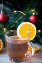 Warm drink with orange on Christmas tree background