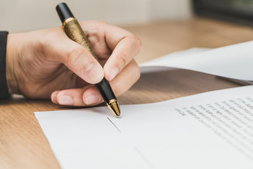 Close up business woman signing terms of agreement document on wooden table, signing concept
