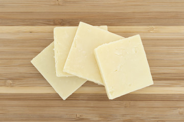 Top view of several slices of sharp cheddar cheese squares on a small wood cutting board.