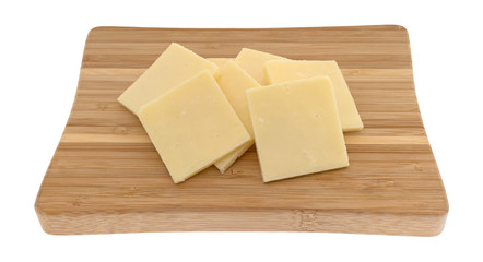 Several slices of sharp cheddar cheese squares on a small wood cutting board isolated on a white background.