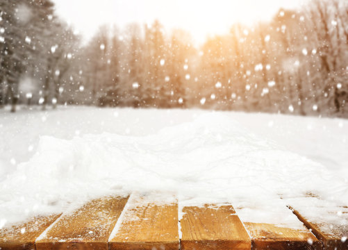 Wooden desk covered by snow and snowy park on background