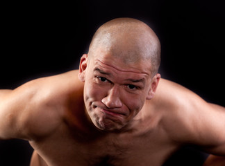 Muscular man topless in a threatening posture