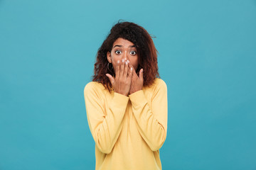 Shocked african woman in sweater covering her mouth