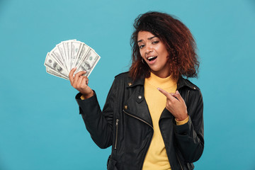 Pleased african woman in leather jacket holding money